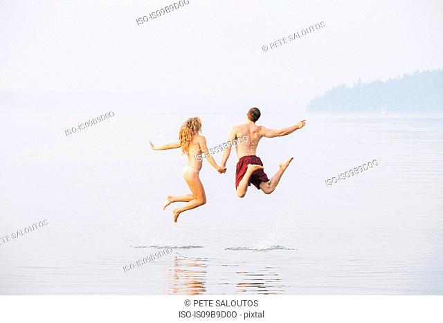 Young couple on beach, holding hands, jumping, mid air, rear view