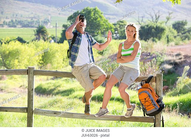 Couple resting on a fence in a rural setting