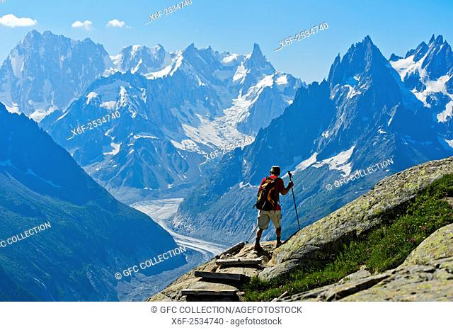 Hiker in the Aiguilles Rouges National Nature Reserve, view at the peaks Grandes Jorasses und Dent du Géant, Chamonix, Haute-Savoie department, France