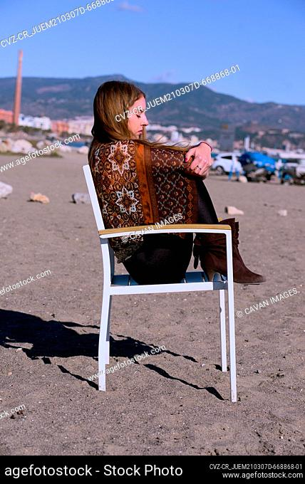 Young girl sitting on a chair in the sand on the beach sunbathes
