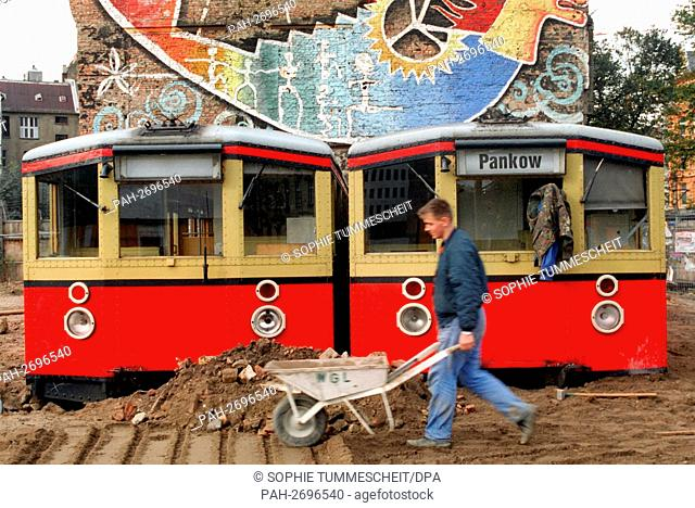 "On October 15, 1997, construction workers put down old S-Bahn cars in the sand in front of the back wall of the alternative Berlin cultural center """"Tacheles"""""