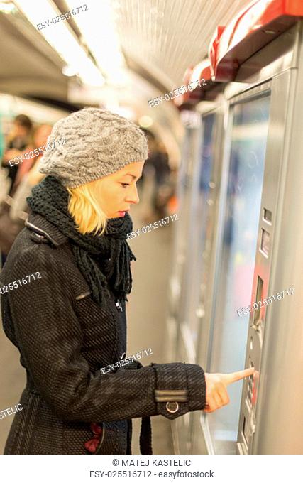 Casually dressed woman wearing winter coat, buying metro ticket at the ticket vending machine. Urban transport