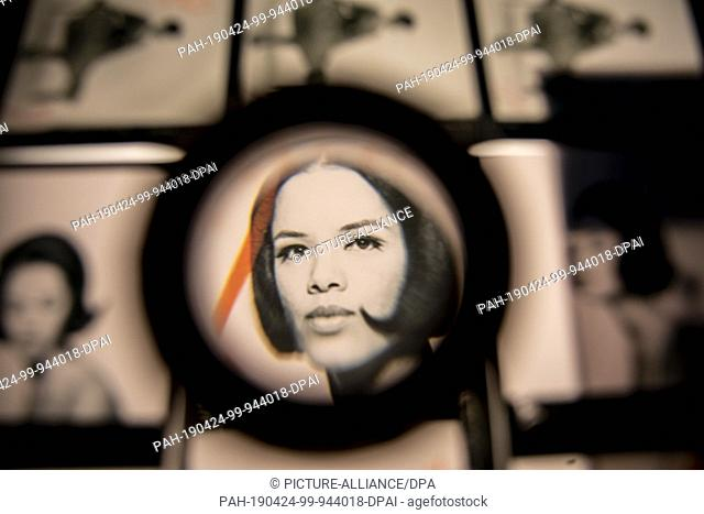 """24 April 2019, Berlin: A portrait on a contact print can be seen through a magnifying glass in the exhibition """"""""The Black Image Corporation"""""""" in the..."""