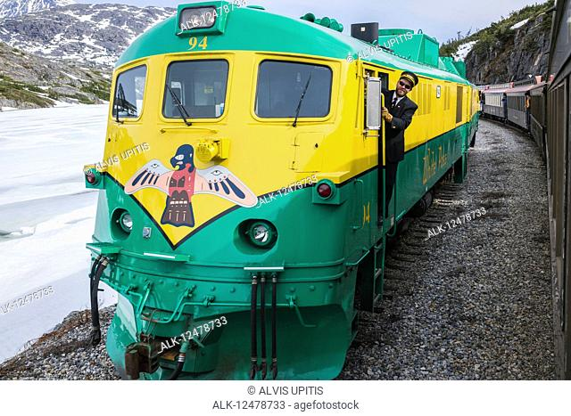 Railroad conductor rides the diesel White Pass Railroad engine on return to Skagway, Southeast Alaska; Skagway, Alaska, United States of America