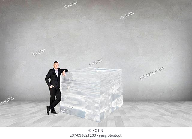 Businessman near big ice cube in the gray room