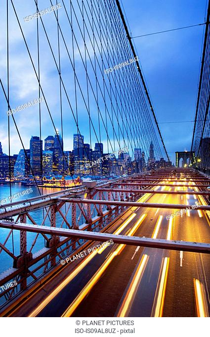 Brooklyn Bridge with traffic at dusk and downtown skyscrapers, New York City, USA