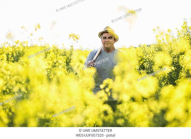 Farmer holding tool in rape field