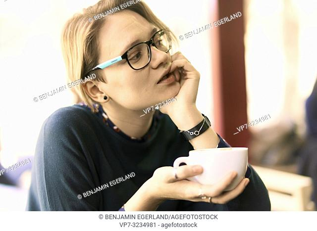 playful woman with coffee cup, taking a break in café, Munich, Germany