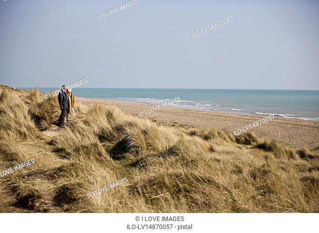 A senior couple walking amongst sand dunes, looking out to sea