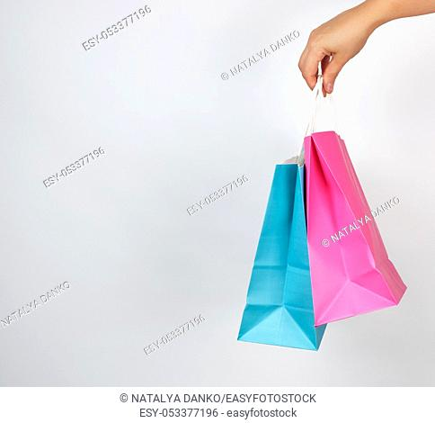 female hand holding colored paper shopping packaging bags on white background, concept of seasonal sales