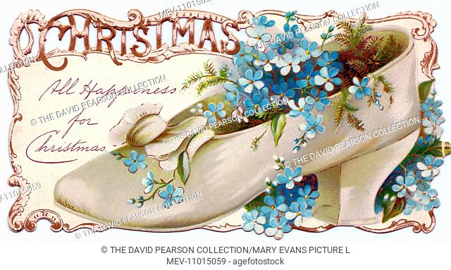 Blue forget-me-nots growing in a white shoe on a cutout Christmas card