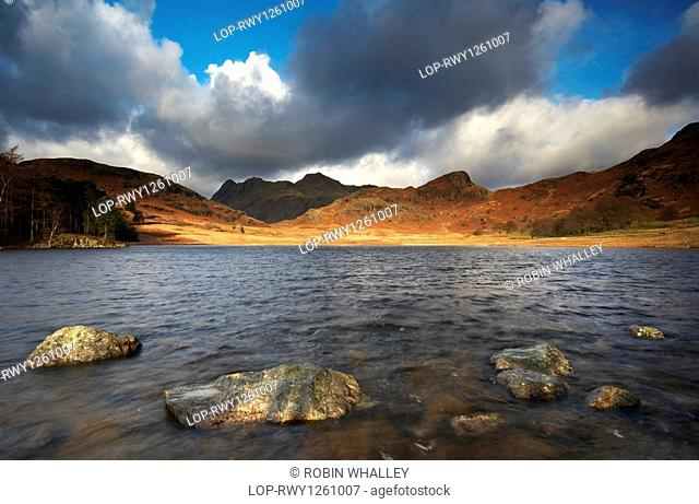 England, Cumbria, Blea Tarn, Sunlight lighting up the distant shore of Blea Tarn, looking towards the Langdale Pikes in the Lake District