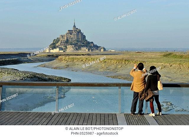 France, Lower Normandy Region, Manche Department, Mont St-Michel seen from the dam on Couesnon river, couple of Asian visitors taking a picture