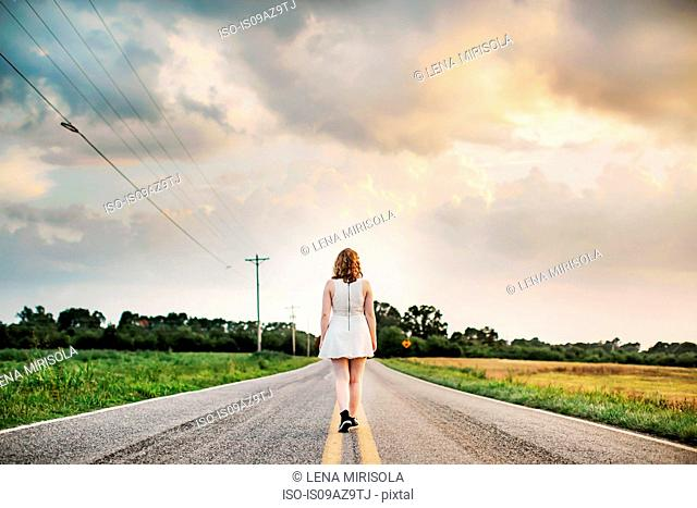 Rear view of woman walking down centre of rural road