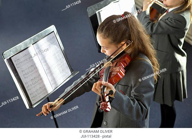 High school student playing violin at sheet music in music class
