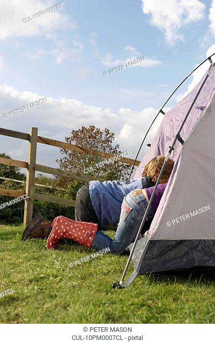Boy and girl climbing into tent
