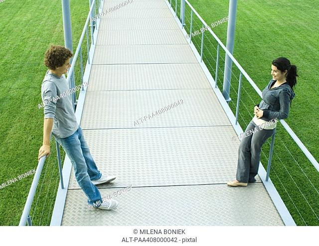 Teenage couple standing face to face on walkway, full length, high angle view
