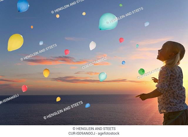 Girl watching balloons floating in evening sky