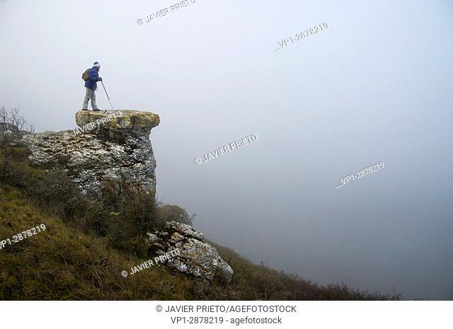 A woman walks through the fog the remains of the archaeological site of Castro Cildá. The Las Loras World Geopark. Near the small village of Olleros de Pisuerga