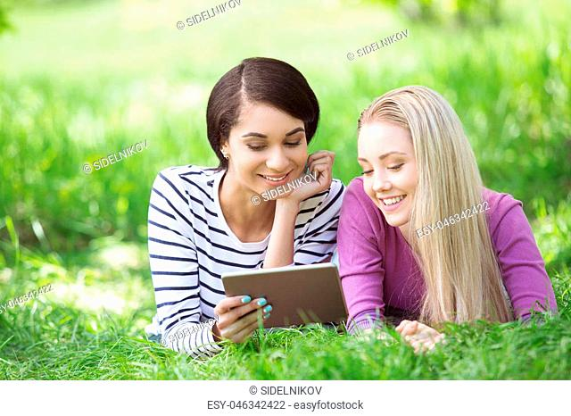 Nice looking young women outdoors. Women using tablet computer. Beautiful green park as a background