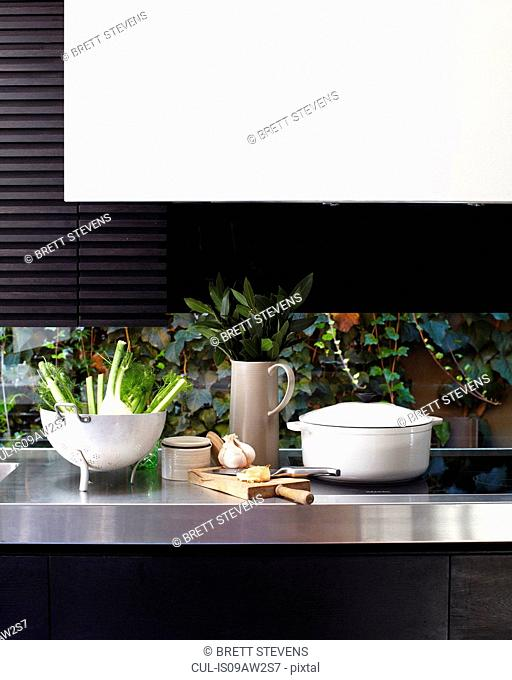Kitchen counter and hob with chopping board and vegetables in colander