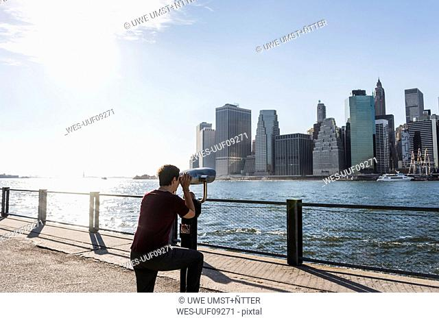 USA, Brooklyn, woman looking at Manhattan skyline with coin operated binoculars