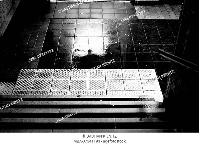 The dark steps of a station tunnel with puddles and damp walls