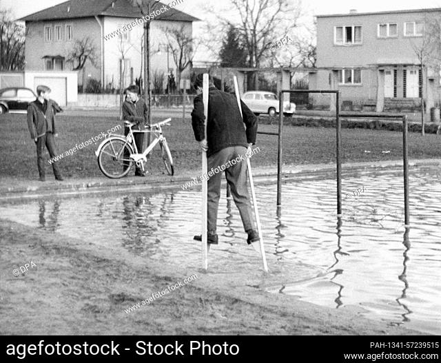 In March 1963 a boy walks with self-made stilts across a flooded children's playground in Frankfurt am Main. | usage worldwide
