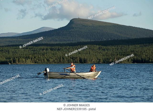 People rowing on lake