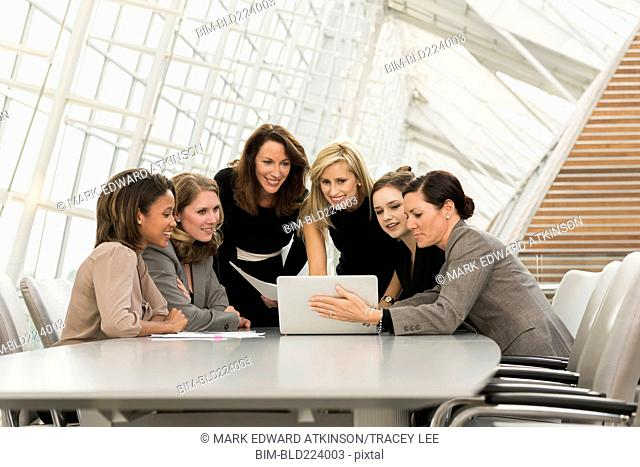 Busy businesswomen using laptop in meeting