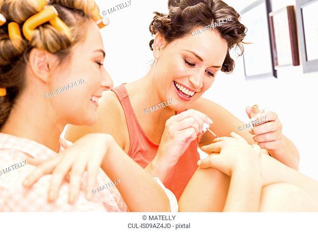 Two female friends, foam rollers in hair, painting fingernails