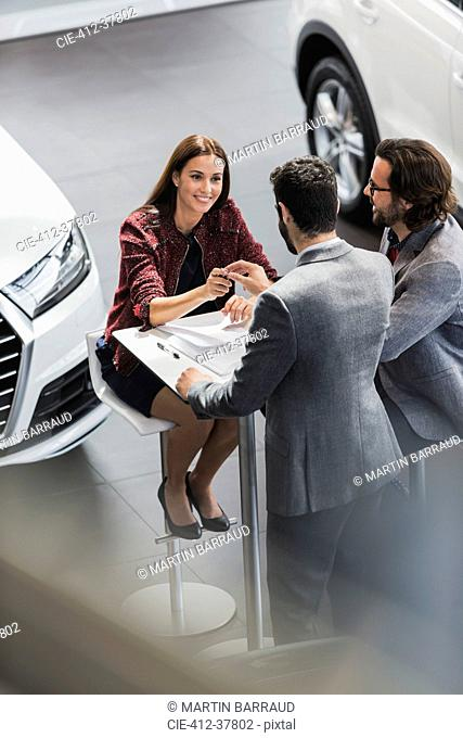 Car salesman giving car keys to smiling female customer in car dealership showroom