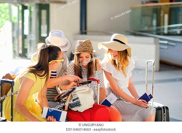 Company of young tourists in the waiting room at the station. Girls sit on a bench. Near them there is their baggage. Girlfriends briskly discuss something
