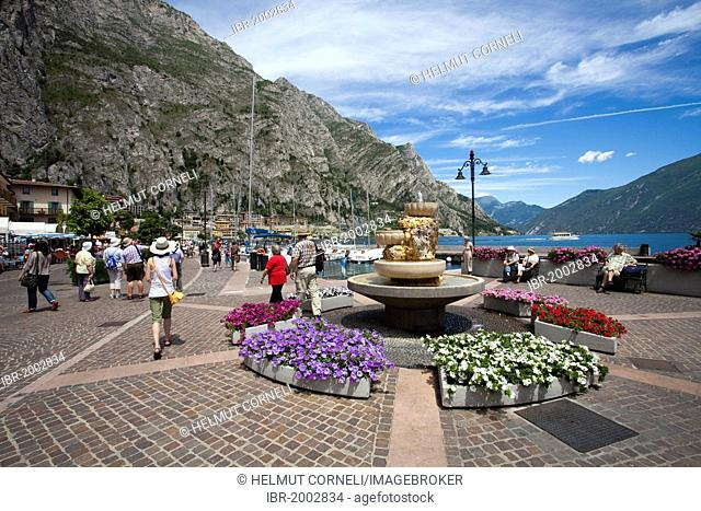 Fountain with flowers on the lakeside promenade, sailing boats in the harbour, Limone sul Garda, Lake Garda, province of Brescia, Lombardy region, Italy, Europe