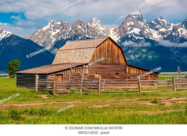 Old mormon barn in Grand Teton Mountains with low clouds. Grand Teton National Park, Wyoming, USA