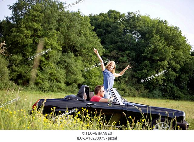 A young couple driving in a convertible black sports car, woman with her arms in the air
