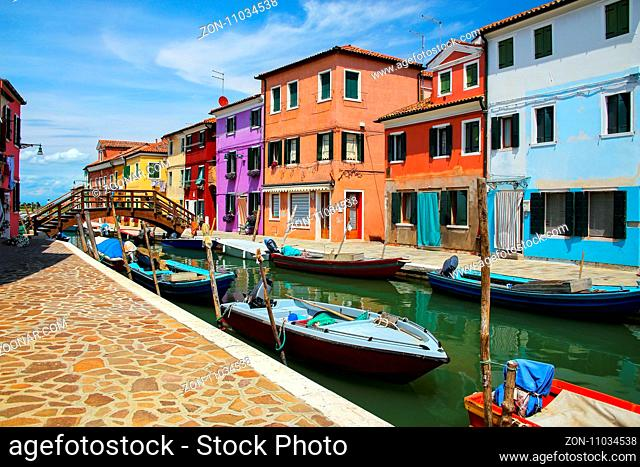 Colorful houses by canal in Burano, Venice, Italy. Burano is an island in the Venetian Lagoon and is known for its lace work and brightly colored homes