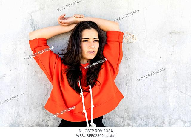 Young contemporary dancer wearing red hoodie shirt in front of a wall