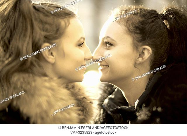Two young sisters looking at each other outdoors in sunlight, face to face, in Munich, Germany