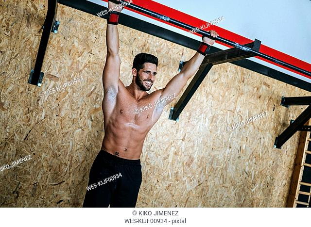 Smiling man doing exercises in gym