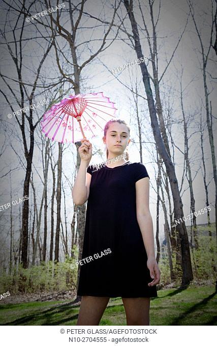 Teenage girl outside, holding a parasol