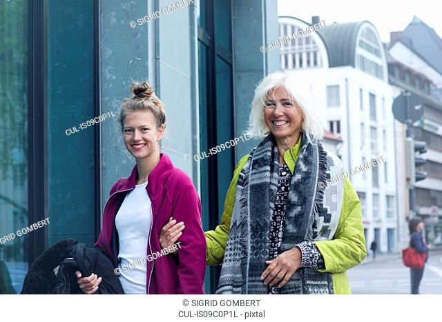 Mature woman and daughter strolling arm in arm on city street, portrait