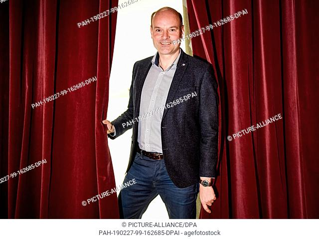 27 February 2019, Hamburg: Axel Schneider, director of the Hamburger Kammerspiele, looks through the curtain of the theatre stage during a photo shoot