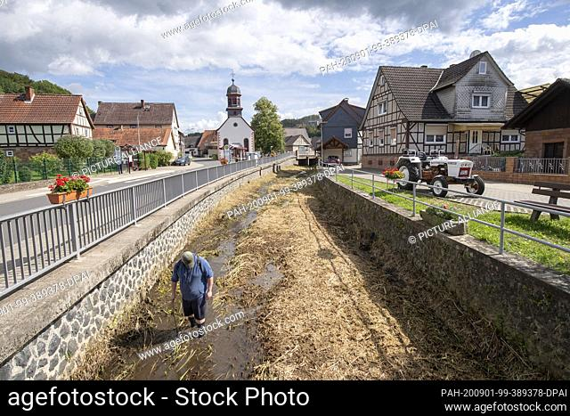 """01 September 2020, Hessen, Bergheim: With a stick in his hand a man wades through the knee-deep water of the """"""""Bleiche"""""""" in Bergheim near Ortenberg in the..."""