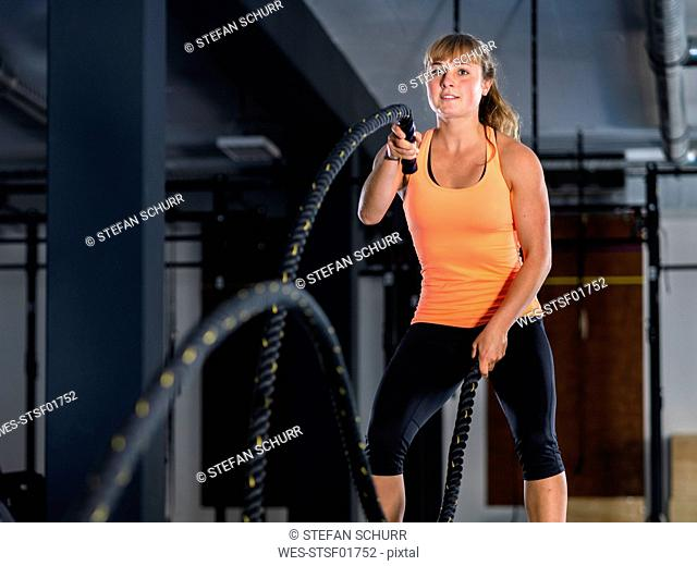 Athletic young woman exercising with battle ropes at gym