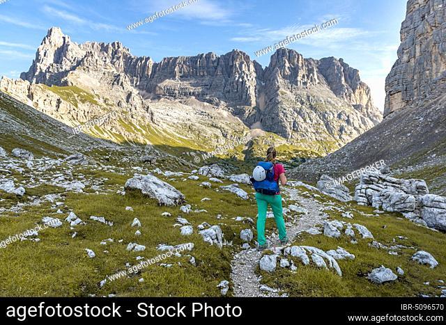 Young hiker on a hiking trail, Sorapiss Circumambulation, behind ridge, Mount Punte Tre Sorelle, Dolomites, Belluno, Italy, Europe