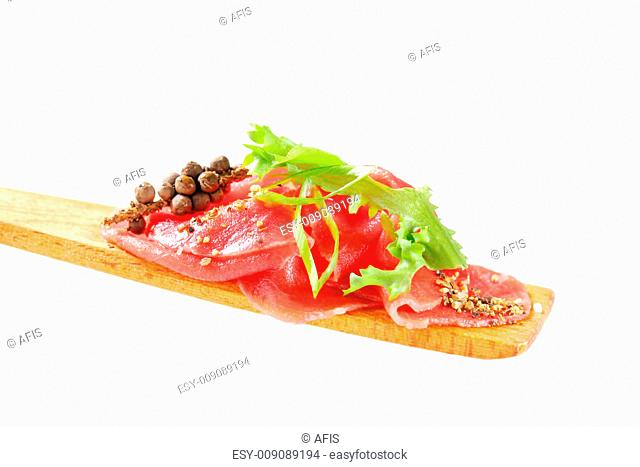 Thin slices of raw beef on wooden spatula