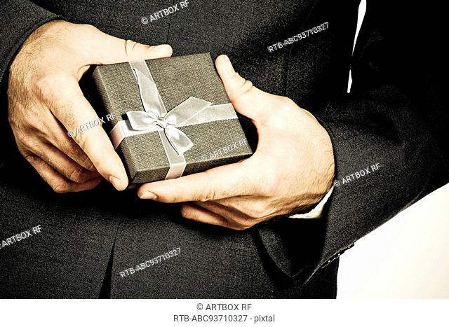 Mid section view of a businessman holding a gift