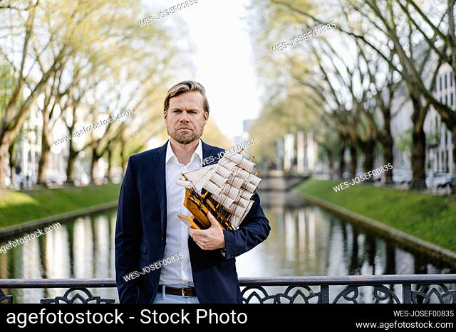 Businessman holding model ship at a channel