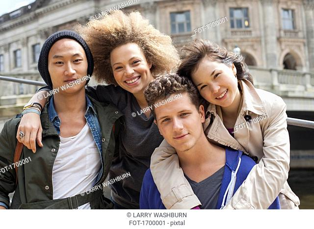 Low angle portrait of smiling young multi-ethnic friends against Bode Museum, Berlin, Germany